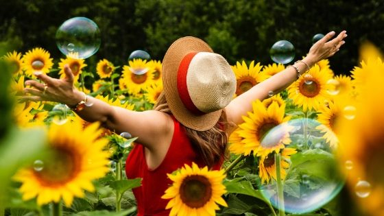 Woman in red dress and straw hat in a field of sunflowers from the post How to Cheer Yourself Up.