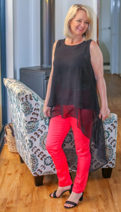 Mature woman in orange pants and black top from the post Fifty Plus Women's Fashion