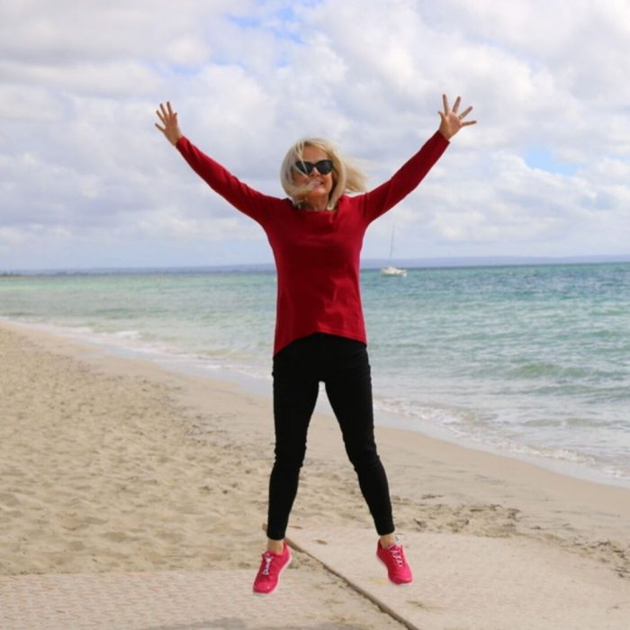 Woman jumping for joy, fully clothed, on beach