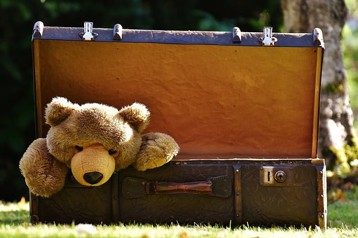 Suitcase and teddy bear in post  International Travel Packing list