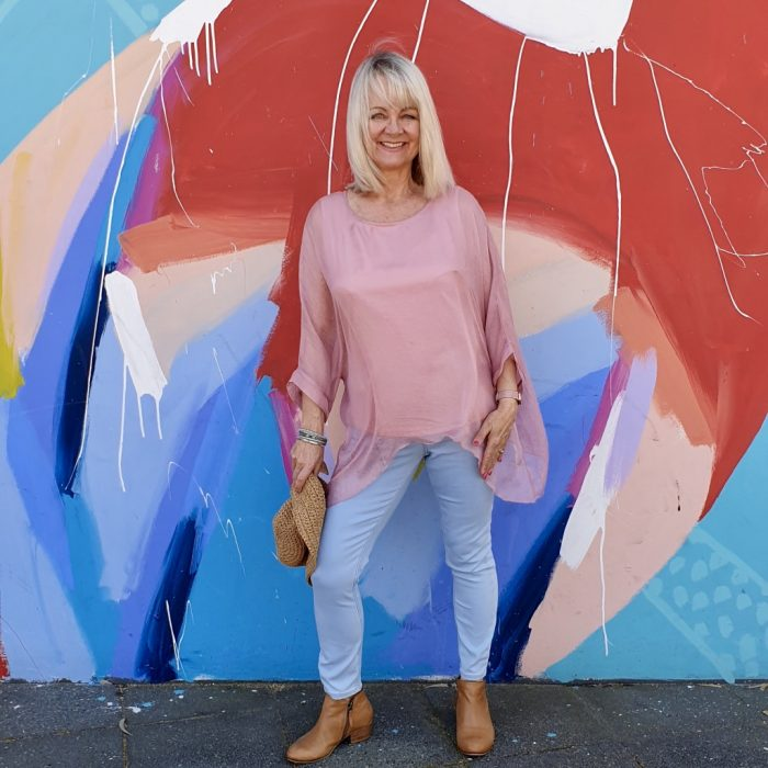 Woman in jeans in front of colourful mural. From post How to look Stylish - Simple Fashion Tips