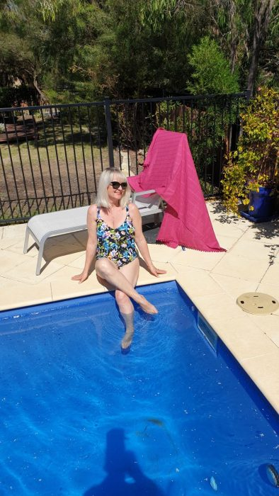 woman in swimsuit relaxing by swimming pool