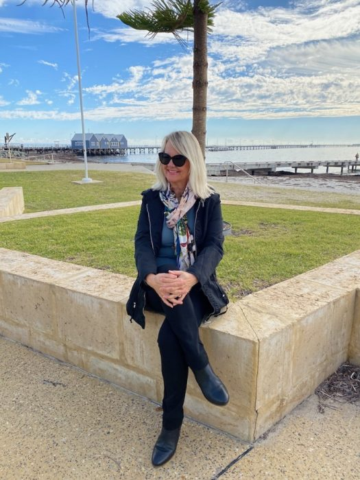 Woman wearing ponte pants and black jacket sitting near Busselton Jetty and beach. Post - Fashion for older women