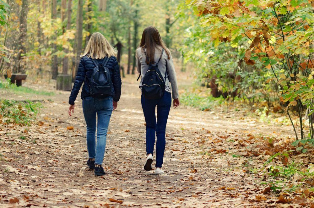 Two women walking away from camera wearing jeans