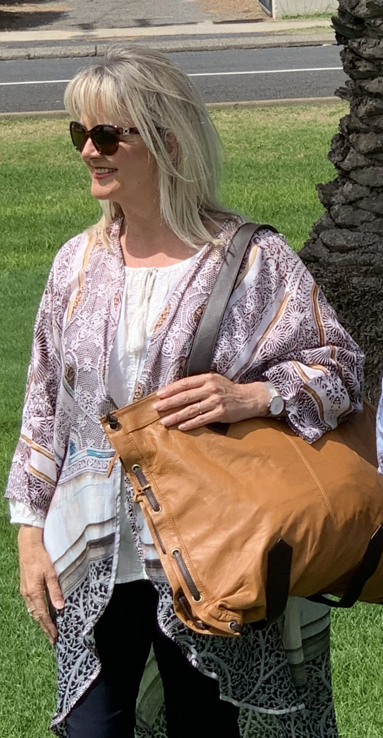 Woman dressed in kimono with leather handbag from the blog post How to Look Sleek and Chic.