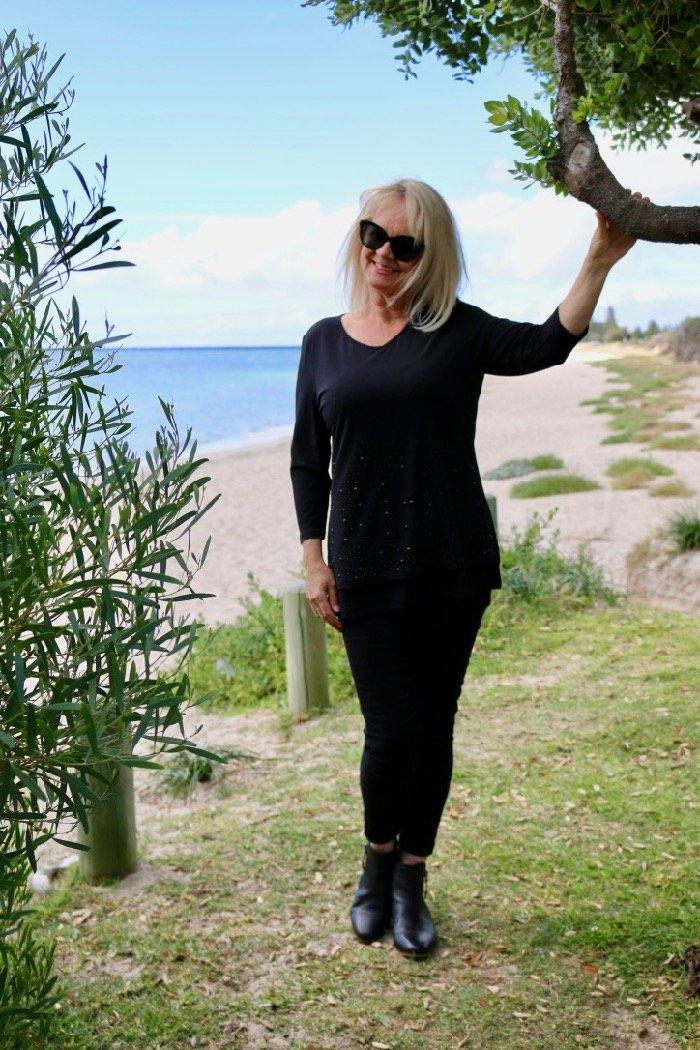 Woman wearing ponte leggings and black top near the ocean.
