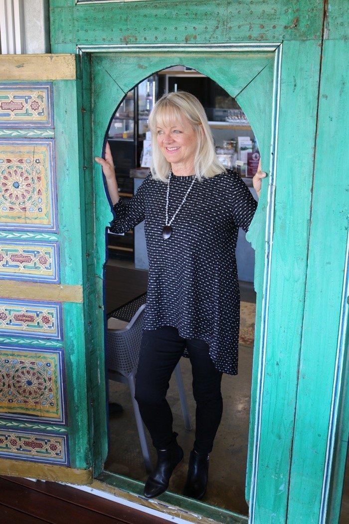 Woman wearing ponte leggings and polka dot blouse posing in a green door.