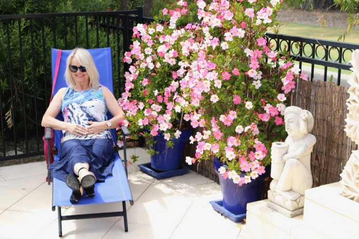 fifty-plus-fashion, lady reclining on a deck chair in blue skirt and colourful top.