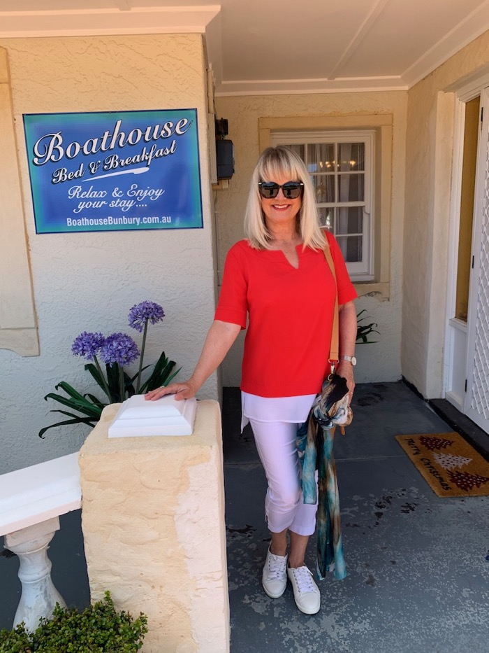 Lady in red blouse standing outside a Bed and Breakfast. Showing example of a weekend outfit.