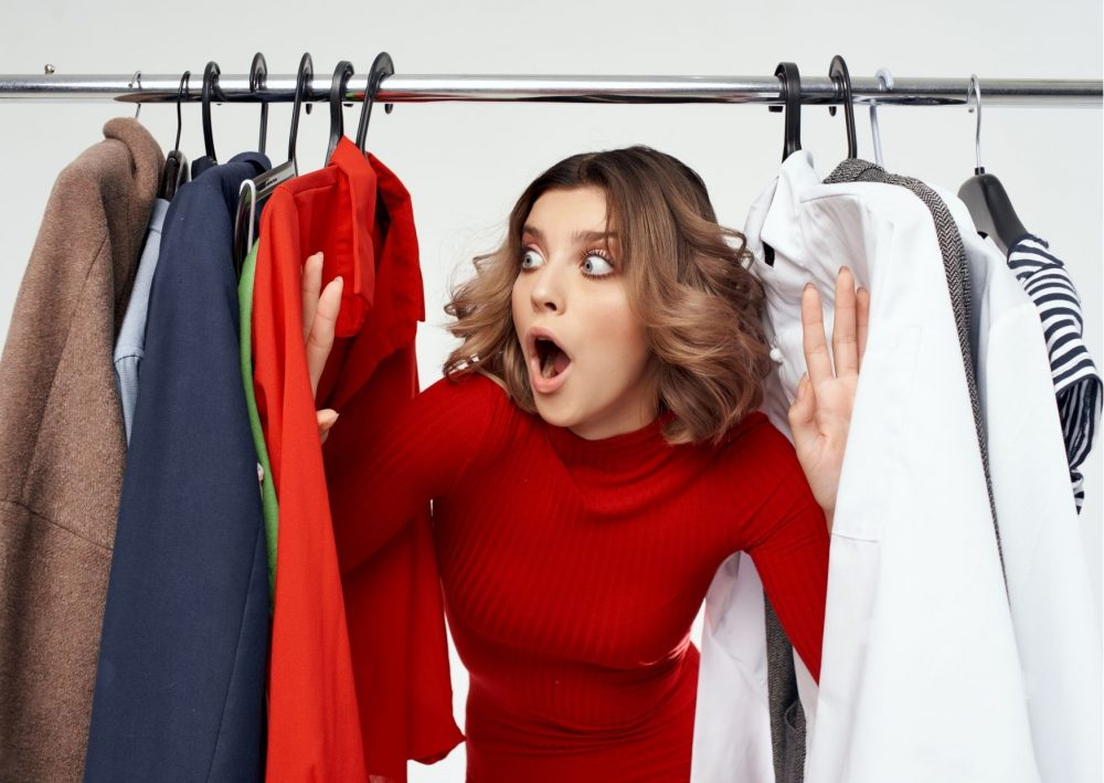 woman looking through clothes on a rail. Blog Post How to Look Stylish Everyday on a Budget.